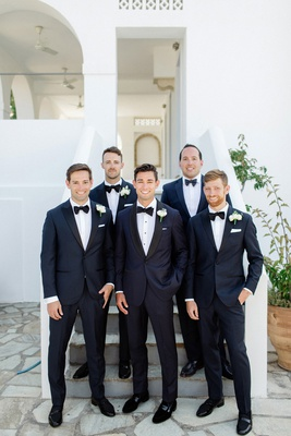 groom and groomsmen in navy tuxedos with black lapels and bow ties.
