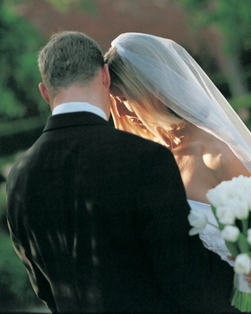 Groom's black suit and bride's white veil