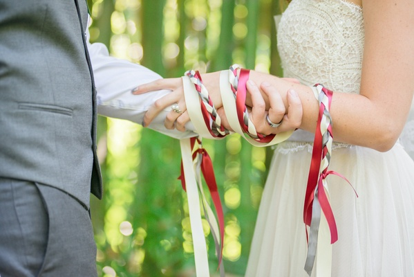 hand-fasting ribbon chord silk red white gray tied around hands celtic wedding tradition ceremony
