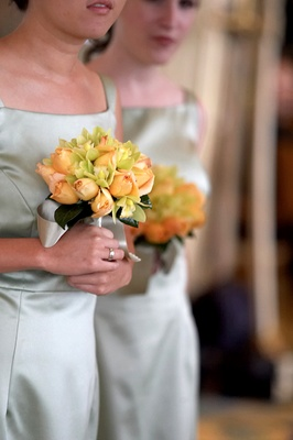 Bridesmaids hold small bouquets of orange and green flowers