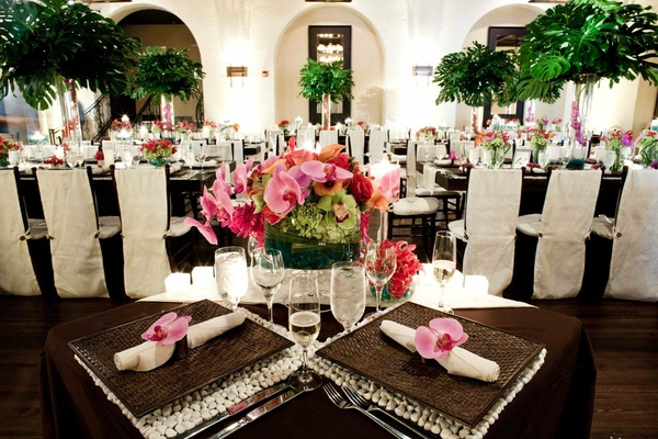 Tropical wedding table decoration with orchids and pebble placemat