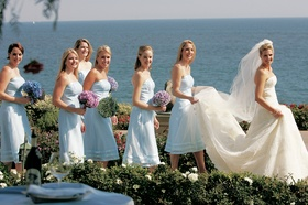Bridesmaids holding bride's train with ocean background