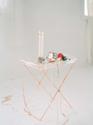 a contemporary style copper and glass table with candles a geometric shape and a flower bar cart