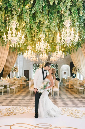 wedding portrait with reception decor bride groom kiss on white gold dance floor checkerboard