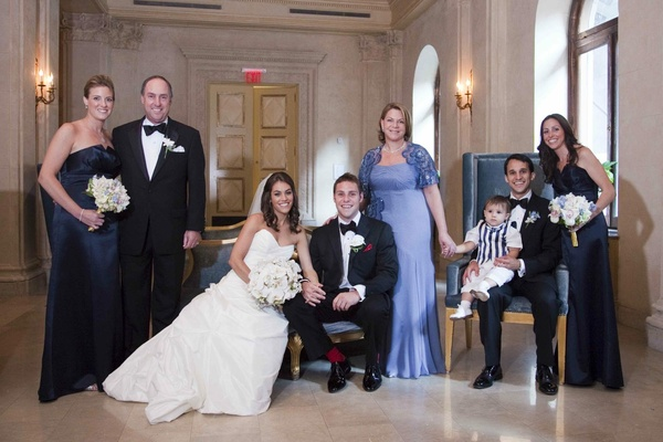 Bride in a Romona Keveza dress, veil, and white bouquet with groom in black tuxedo with family