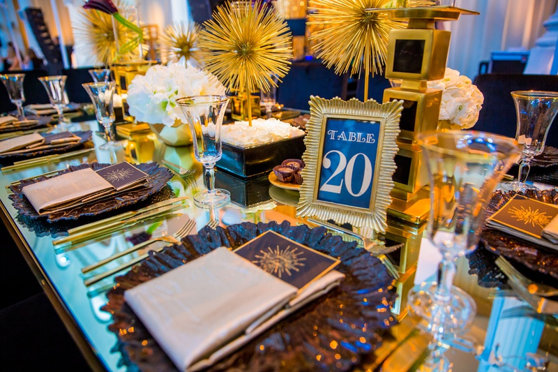 art deco inspired wedding reception with black and gold, table numbers in frame