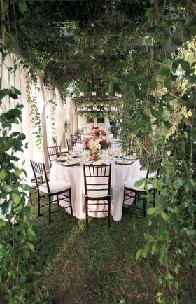 Backyard dinner tables surrounded by lush greenery
