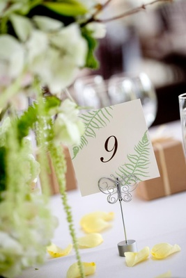 Wedding reception table number decorated with fern fronds