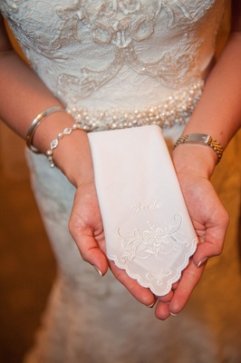 Bride holding scallop edge handkerchief with bride embroidery