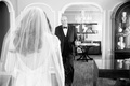 Black and white photo of father of the bride's reaction to daughters wedding dress holding champagne