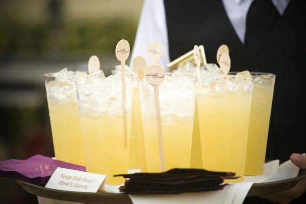 Yellow wedding drinks with custom swizzle sticks