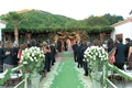 Green aisle runner leads to chuppah on terrace