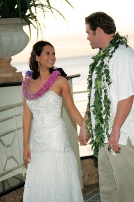 bride wearing pink lei and groom wearing green lei