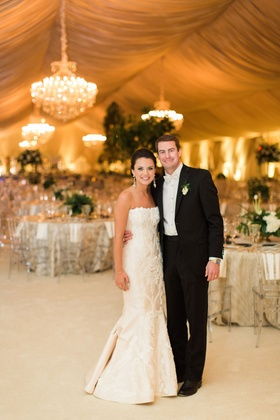 Bride in strapless romona keveza wedding dress groom in suit with white bow tie drapery chandeliers