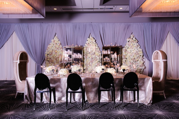 Wedding Reception With Long Head Table In Silver Tablecloth, Black Ghost  Chairs, Floral Panels ...