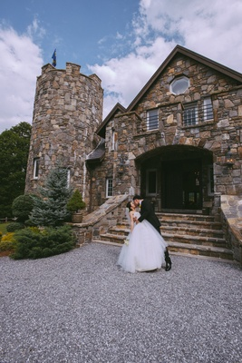Man dipping wife in front of stone castle on gravel