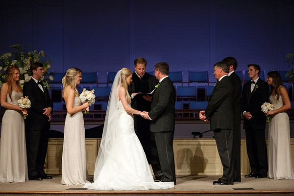 Bride in a strapless fit-and-flare wedding dress and veil with groom in a black tuxedo at altar