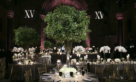 Wedding reception at Cipriani Wall Street with red uplighting, greenery centerpiece, white orchids