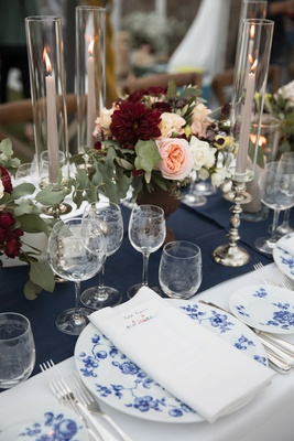 wedding reception table with blue floral china pattern, navy table runner, marsala and blush florals