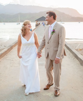 Bride and groom holding hands on pier in Kauai
