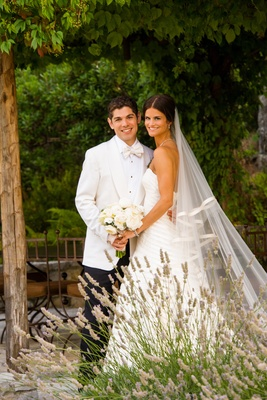 Bride in a strapless Vera Wang gown with groom in a tuxedo with white coat and bow tie