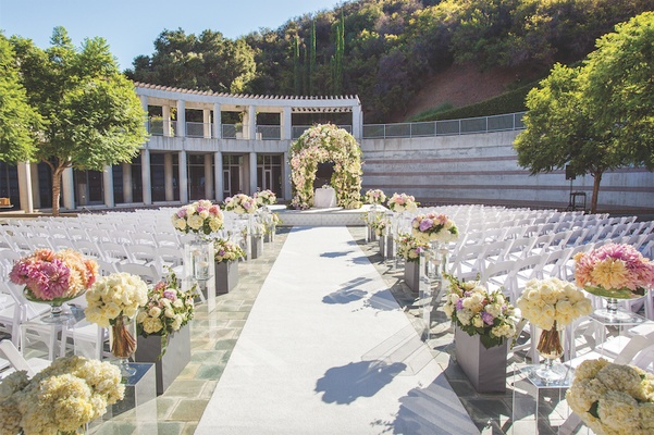Large floral chuppah with flower arrangements along aisle