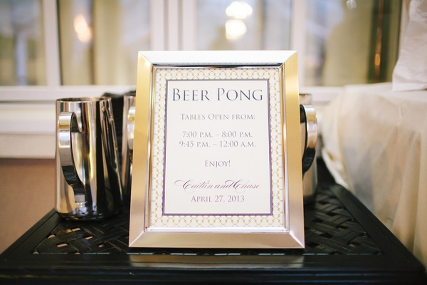 Silver framed sign of beer pong table hours at wedding