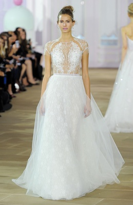 Soft ball gown with Chantilly illusion bodice, jewel neckline, beaded cap sleeve and natural waist.