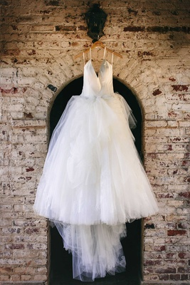 white tulle ball gown with plunging halter neckline hanging up before ceremony