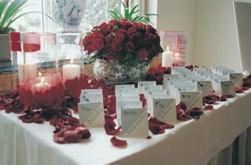 place cards surrounded by red roses and petals