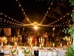 outdoor reception area long table white linens candelabra strings lights guests dancing night