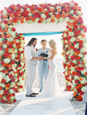 "CJ ""Lana"" Perry and Miroslav ""Rusev"" Barnyashev under arch CJ's dad officiant hydrangea rose daisy"