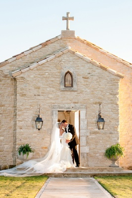 Bride and groom in front of old brick church in Texas