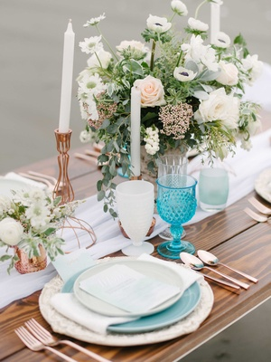 blue and white tablescape featuring rose gold and green accents in the candles floral arrangement