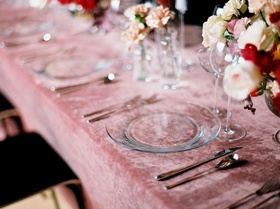 Wedding reception pink velvet linen tablecloths with clear charger plates and pink ivory flowers