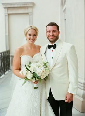 Bride in strapless oscar de la renta wedding dress white bouquet updo hair up groom in white tuxedo