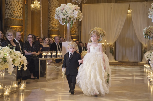flower girl in full ruffled skirt holding hands with younger ring bearer in black suit