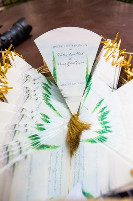 Wedding ceremony programs in the form of fans with watercolor paintings of trees and gold tassels