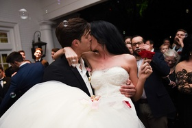 bride in nardos deisgns lace mermaid gown holding red rose, held by groom, kisses, bubbles