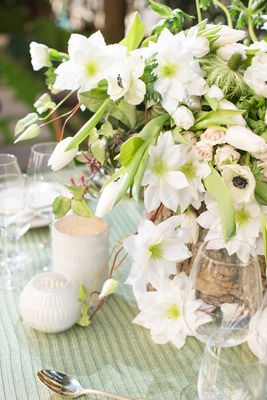 green and white anemone floral arrangement centerpiece with tree stump vase and small white candles