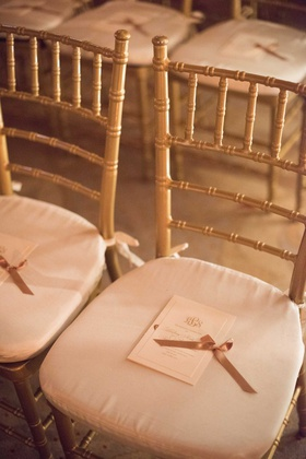 wedding ceremony gold chairs white cushions monogram ceremony program gold ribbon