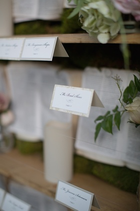 Wedding place cards suspended in front of a garden-themed bookcase