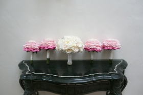 Pink glamelia bouquets and white wedding bouquet on black table