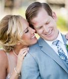 Bride in a Love Marley dress with illusion neckline, lace bodice with groom in grey suit