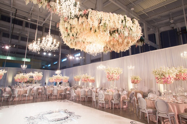Wedding reception chandeliers and flowers floating over custom dance floor pink tables