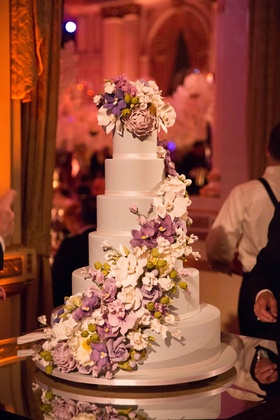 Six layer wedding cake with purple white orchid peony rose sugar flowers cascading down side