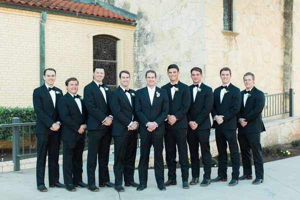 Groom in black suit with white bow tie and groomsmen in black suits with black bow ties cowboy boot