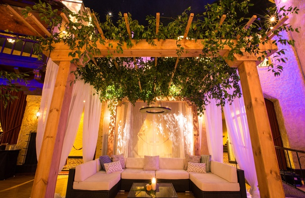 Wedding reception lounge area wood pergola greenery chandelier sectional with coffee table candle