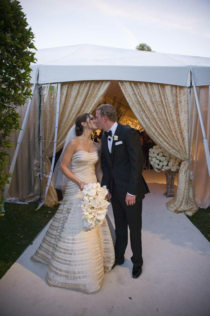 Bride in a champagne Vera Wang gown kisses groom in a black tuxedo and bow tie