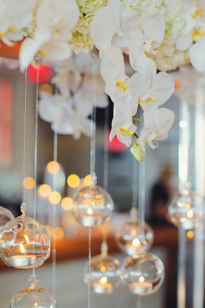 a08750f2fcb7f ... Wedding reception with tea lights in glass spheres hung from arch of  white orchids and hydrangeas ...